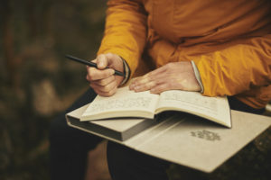 close up of hand writing in journal, orange jacket, outside